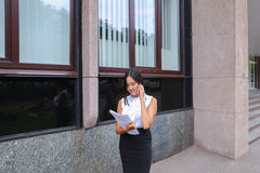 Serious young asian business woman, student talks on phone, hold Royalty Free Stock Photography