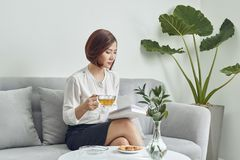 Free Serious Young Asian Girl In Blouse And Skirt.sitting On Sofa And Drinking Tea While Reading Book In Living Room Royalty Free Stock Photo - 138731665