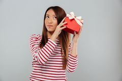 Serious young asian lady standing isolated holding gift. Image of serious young asian lady standing isolated over grey wall. Looking aside holding gift Royalty Free Stock Image