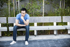Serious young asian man on bench Royalty Free Stock Images