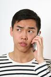 Serious young Asian man using a smartphone Royalty Free Stock Photography