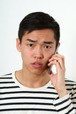 Serious young Asian man using a smartphone Stock Photography