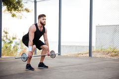 Serious young bearded man athlete exercising and lifting barbell outdoors Royalty Free Stock Images