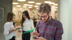 Serious young bearded man in glasses and casual plaid shirt stands in a hub and focused on texting message. Two female. Serious young bearded man stands in a hub stock video footage
