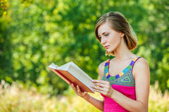 Serious young beautiful woman holding red book Stock Image