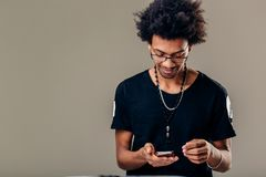 Always in touch. man holding smart phone and looking at it with smile. Serious young black male in trendy rectangular glasses looking through pcitures via social Royalty Free Stock Photo