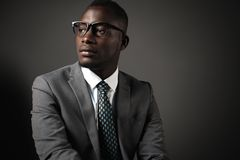 Serious young black man with glasses and gray business suit. Emotional business portrait royalty free stock images