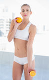 Serious young blonde model holding an orange and a half Stock Photo