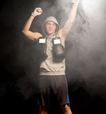 Serious young boxer raising his fists Stock Photography