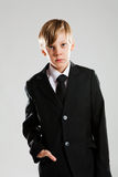 Serious young boy in black suit Royalty Free Stock Photo