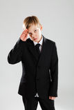 Serious young boy in black suit saluting Stock Photos