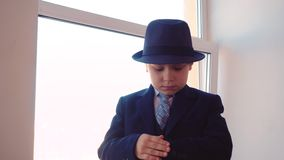 Serious young boy in business suit and hat looking wrist watch on window background in office. Portrait business boy stock video
