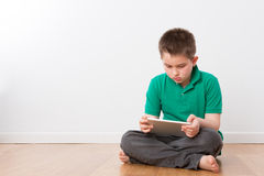 Serious Young Boy on the Floor Busy with Tablet Royalty Free Stock Photography