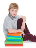 Serious young boy near books Stock Photo