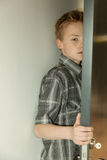 Serious young boy peering around a door Stock Photography