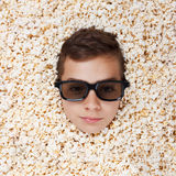 Serious young boy in stereo glasses looking out of popcorn Stock Photos