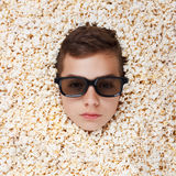 Serious young boy in stereo glasses looking out of popcorn Stock Photo