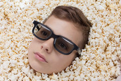 Serious young boy in stereo glasses looking out of popcorn Royalty Free Stock Photos