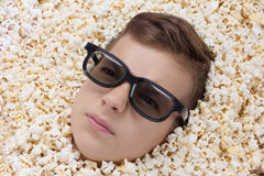Serious young boy in stereo glasses looking out of popcorn Royalty Free Stock Photography