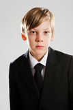 Serious young boy wearing black suit Royalty Free Stock Image