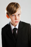 Serious young boy wearing black suit Royalty Free Stock Photo