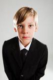 Serious young boy wearing black suit Royalty Free Stock Photography
