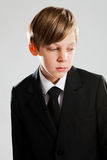 Serious young boy wearing black suit Royalty Free Stock Images