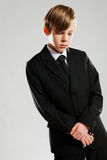 Serious young boy wearing black suit Stock Photography