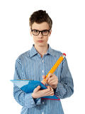 Serious young boy writing on a clipboard. Serious faced boy writing with big yellow pencil on a clipboard Royalty Free Stock Image