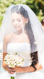 Serious young bride in veil holding bouquet Stock Image