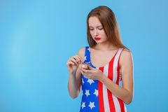 A girl, dressed in bodysuits with an American flag print, unpacks a small gift box. On a blue background. A serious young brunette girl, European-looking Stock Images