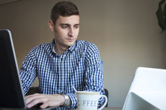 Serious young business man cheking his tablet at home office Royalty Free Stock Image