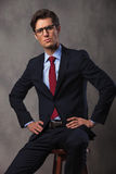 Serious young business man with hands on waist sitting Royalty Free Stock Images