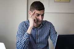 Serious young business man looking worried at laptop screen at home office Royalty Free Stock Photos