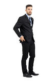 Serious young business man putting mobile phone in his pants pocket side view. Full body length portrait isolated over white studio background Royalty Free Stock Photos