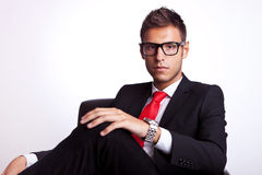 Serious young business man seated Royalty Free Stock Images