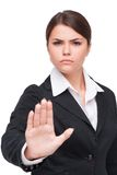 Serious young business woman doing stop gesture Stock Photos