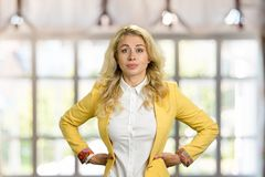 Serious young business woman, hands on hips. Stock Images
