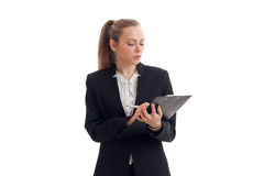 A serious young business woman holding a black Tablet and writes something Royalty Free Stock Photos
