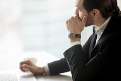 Serious young businessman in deep thought at workplace in office Royalty Free Stock Photo