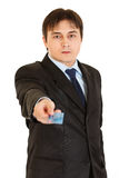 Serious young businessman giving credit card Royalty Free Stock Image