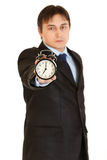 Serious young businessman holding alarm clock Stock Images