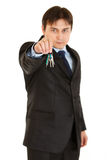 Serious young businessman holding keys in hand Stock Image