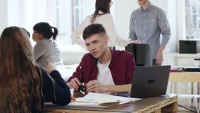 Serious young businessman listening to female colleague talking, sitting at office table in loft trendy coworking. Millennial corporate workers chat, business stock footage