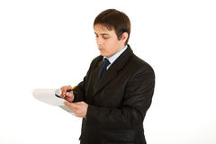Serious young businessman making notes in document Royalty Free Stock Photography
