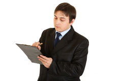 Serious young businessman making notes in document Stock Photos