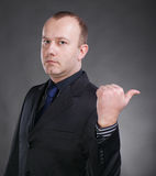 Serious young businessman pointing at something. Portrait of a serious young businessman pointing at something on a gray background stock photography