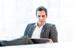 Serious young businessman reading his tablet-pc Stock Images