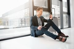 Serious young businessman sit at window and lean to it. He look at phone in his hands. Guy wait for flight in airport. Hall stock photos