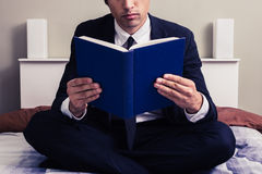 Serious young businessman sitting in bed reading book Stock Images